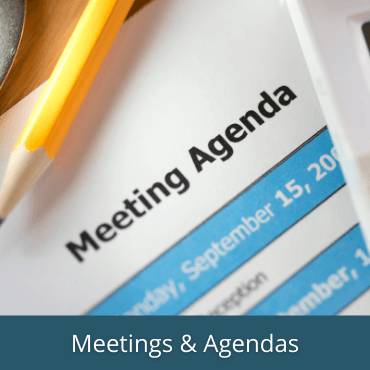 Printed paper entitled, Meeting Agenda, with a pencil and calculator laying next to the title.